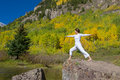 Yoga at maroon bells in autumn a happy woman practicing the scenic fall as a backdrop Royalty Free Stock Image