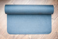 Yoga mat gray isolated on wooden boards Stock Photos