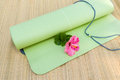 Yoga mat a rolled out halfway with a flower laying on it Royalty Free Stock Photos