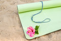 Yoga mat a rolled out halfway with a flower laying on it Stock Photos