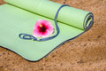 Yoga mat a rolled out halfway with a flower laying on it Royalty Free Stock Image
