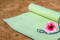 Yoga mat a rolled out halfway with a flower laying on it Royalty Free Stock Photo