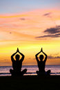 Yoga meditation silhouettes of people at sunset silhouette a couple practicing sitting on a beach in the lotus Royalty Free Stock Images