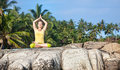 Yoga meditation woman doing lotus pose on the stone at blue sky and tropical background in kovalam kerala india Royalty Free Stock Image
