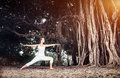 Yoga near banyan tree woman in white costume doing warrior pose big in goa india Stock Photo