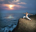 Yoga near the ocean warrior pose by man in white trousers on cliff in kerala india Stock Image