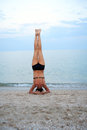 Yoga near sea svelte mature woman standing on her head Royalty Free Stock Images