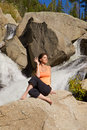 Yoga outdoors a woman practicing near a waterfall Royalty Free Stock Photography