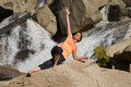 Yoga outdoors a woman practicing near a waterfall Royalty Free Stock Image