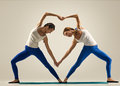 Yoga in pair heart sporty yogi sisters doing fitness training studio shot couple Royalty Free Stock Image