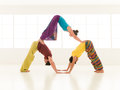 Yoga partner gym vibrant color people dressed in colors perform moves Royalty Free Stock Photography