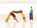 Yoga partner gym vibrant color people dressed in colors perform moves Royalty Free Stock Images