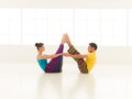 Yoga partners beautiful women with a handsome men dressed in vibrant colors are in white gym Stock Image
