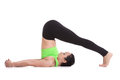 Yoga plow pose beautiful sporty yogi girl practices asana halasana stretches shoulders and spine therapy for backache healthy Royalty Free Stock Photo
