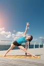 Yoga pose elongated triangle on the background of the sea Stock Photo