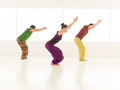 Yoga posture utkatasana three students performing studio light background window Stock Image