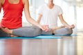 Yoga practice lower part of slim female and men on background meditating in pose of lotus in gym Stock Image