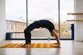 Yoga practice. Man doing bridge pose inside room with panoramic windows. Royalty Free Stock Photo
