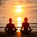Yoga practice, young couple sitting on the beach Royalty Free Stock Image