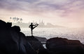 Yoga on the rock man doing one leg balance pose rocks at ocean and mosque background Royalty Free Stock Photo