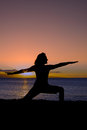 Yoga at sunset a woman doing silhouetted in the on the beach Stock Photo