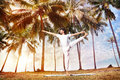Yoga in tropical india by happy indian man white trousers near palm trees kerala Stock Photo
