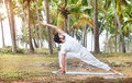 Yoga in tropical india by happy indian man white trousers near palm trees kerala Royalty Free Stock Photo