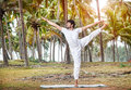 Yoga in tropical india by happy indian man white trousers near palm trees kerala Stock Image