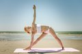 Yoga utthita trikonasana triangle pose by woman in white bikini on a beach with pink mat Royalty Free Stock Images