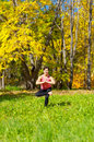 Yoga vrikshasana tree pose woman exercises in the autumn forest Royalty Free Stock Images