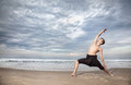 Yoga warrior pose in india by man black trousers on the beach near the ocean Stock Photo