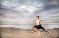 Yoga warrior pose in india by man black trousers on the beach near the ocean Royalty Free Stock Photos