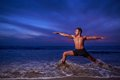 Yoga warrior pose man ocean beach dusk Royalty Free Stock Image