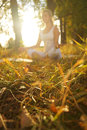 Yoga woman on autumn park background focus on grass blured Royalty Free Stock Photography