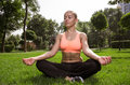 Yoga woman on green grass in lotus pose Royalty Free Stock Photography