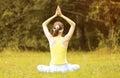Yoga woman meditates outdoors on the grass Stock Photo