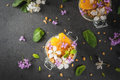 Yoghurt with granola, orange, mint and edible flowers Royalty Free Stock Photo