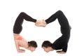 Yogi couple in yoga fierce bird pose profile of two sporty people doing backbend handstand standing chin balance asana ganda Royalty Free Stock Image