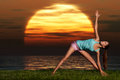 Yogi sunrise a sportive beautiful woman training yoga on the beach at dawn Royalty Free Stock Photos