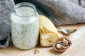 Yogurt with banana and nuts in a glass jar for healthy morning meal, selective focus Royalty Free Stock Photo