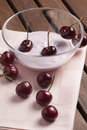 Yogurt with cherries cup of on wooden table and pink background Royalty Free Stock Images