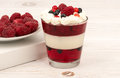 Yogurt dessert in glass with cream, jell, raspberries and blueberries on wooden background. Royalty Free Stock Photo