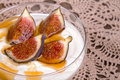 Yogurt with figs and honey greek in a glass bowl over old lace tablecloth Royalty Free Stock Photos
