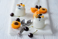 Yogurt in a glass, apricots and ripe cherries Royalty Free Stock Photo