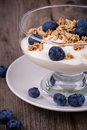 Yogurt with granola and blueberries fresh in glass bowl over old wood background vintage effect Stock Image