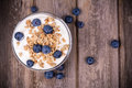 Yogurt with granola and blueberries fresh in glass bowl over old wood background vintage effect Stock Photography