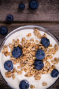 Yogurt with granola and blueberries fresh in glass bowl over old wood background vintage effect Stock Images