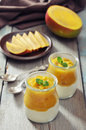 Yogurt with mango and mint in glass jars on wooden background Stock Photography