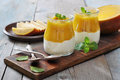 Yogurt with mango and mint in glass jars on wooden background Royalty Free Stock Photo