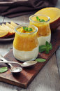 Yogurt with mango and mint in glass jars on wooden background Royalty Free Stock Photos